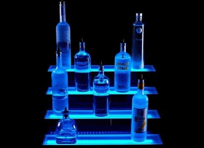 oświetlona niebieskim LEDem półka z butelkami