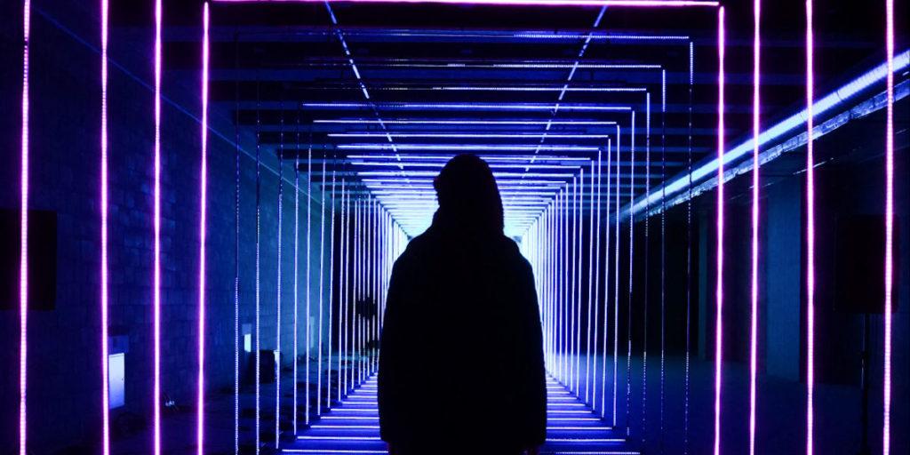 człowiek stojący w tunelu oświetlonym kolorowym światłem LED